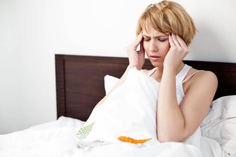 kobieta w łóżku trzymająca się za głowę