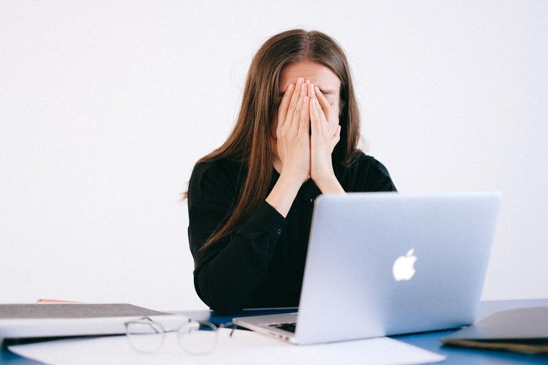 kobieta przed monitorem zakrywa twarz dłońmi