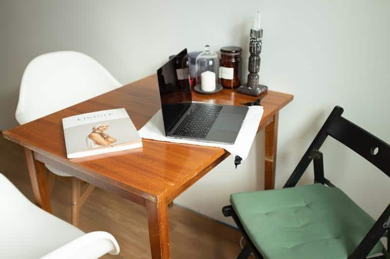 krzeslo, stół a na nim laptop i dokumenty