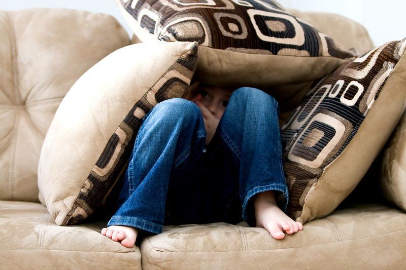 kobieta na kanapie schowana pod poduszkami
