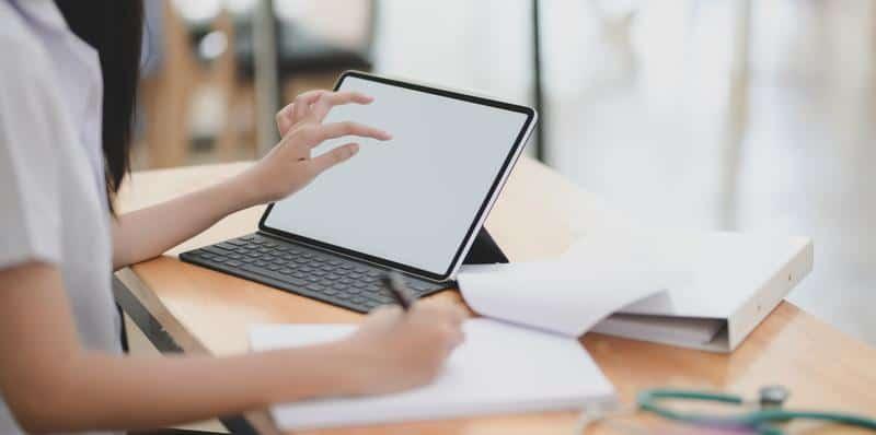 kobieta pisze coś na kartce i patrzy na laptopa