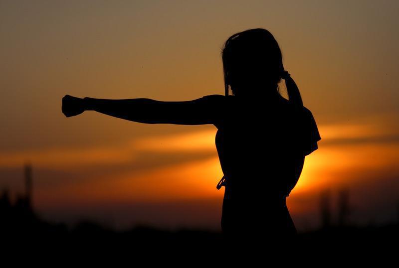 kobieta ćwiczy uderzenie pięścią gdy słońce zachodzi