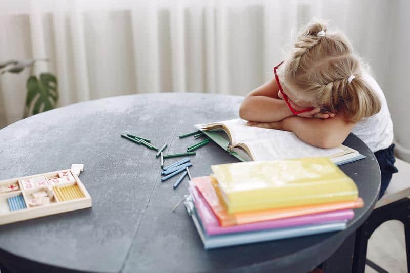 dziecko przy stercie książek przy stole
