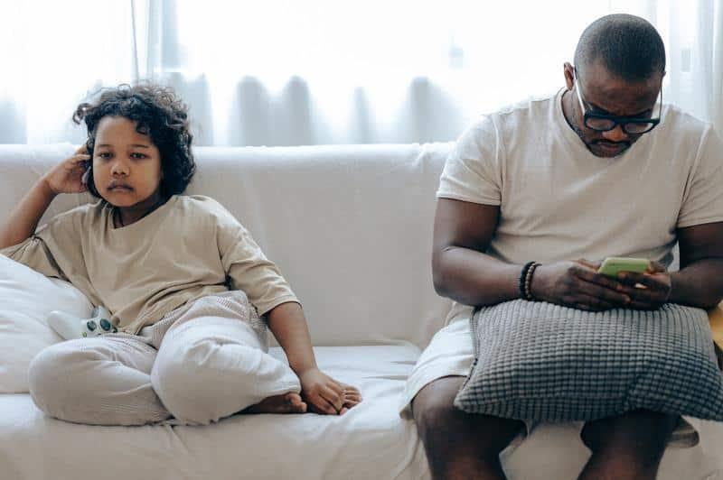 dziecko obok ojca zajętego smartfonem