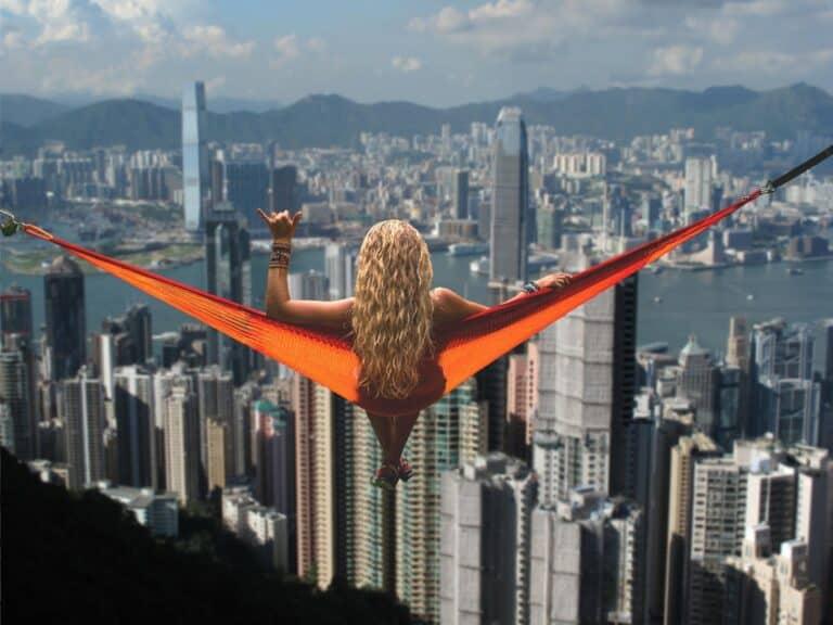 kobieta siedzi na hamaku i patrzy z góry na wieżowce miasta