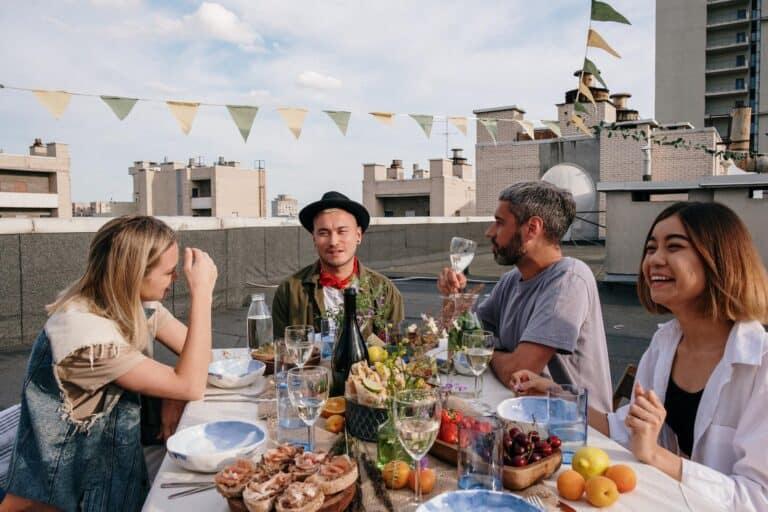 4 ludzi spożywa posiłek przy stole na tarasie budynku
