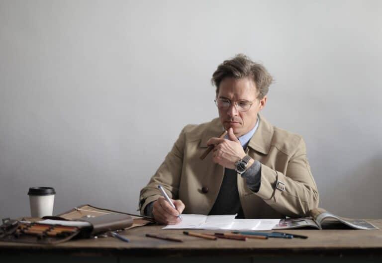 mężczyzna przy biurku z cygarem w dłoni