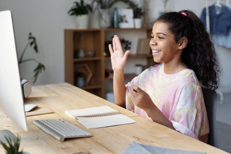 dziewczynka przed komputerem z podniesioną do góry dłonią