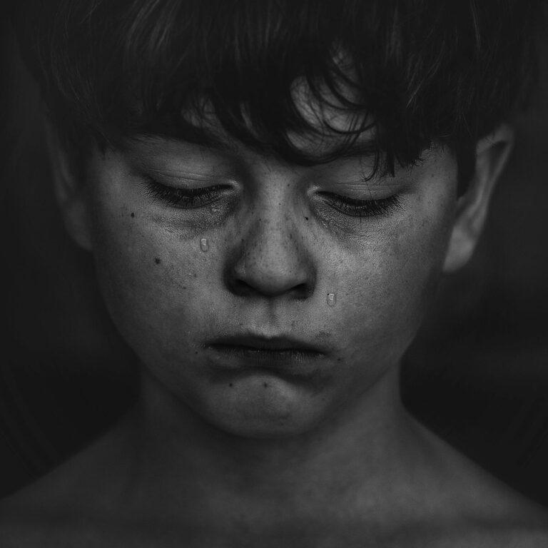 smutny chłopiec patrzy w podłogę