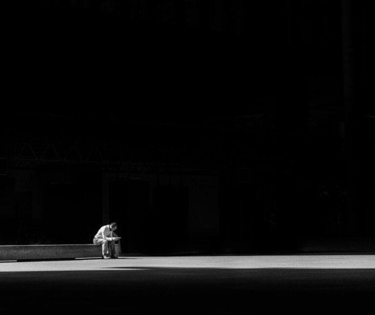 mężczyzna siedzi na murku w ciemności i patrzy w ziemię