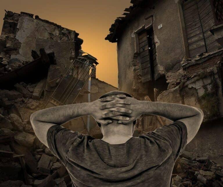mężczyzna trzyma się za głowę dłońmi a twarz ma zwróconą na ruiny