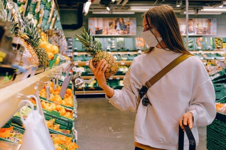 kobieta w masce w sklepie ogląda ananasa