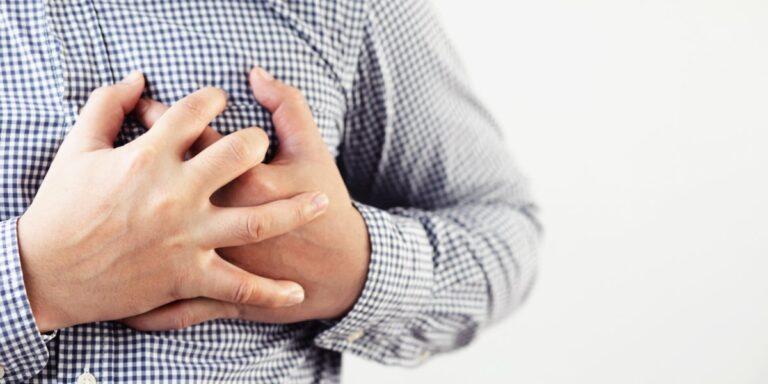 mężczyzna trzyma dłonie w okolicach serca