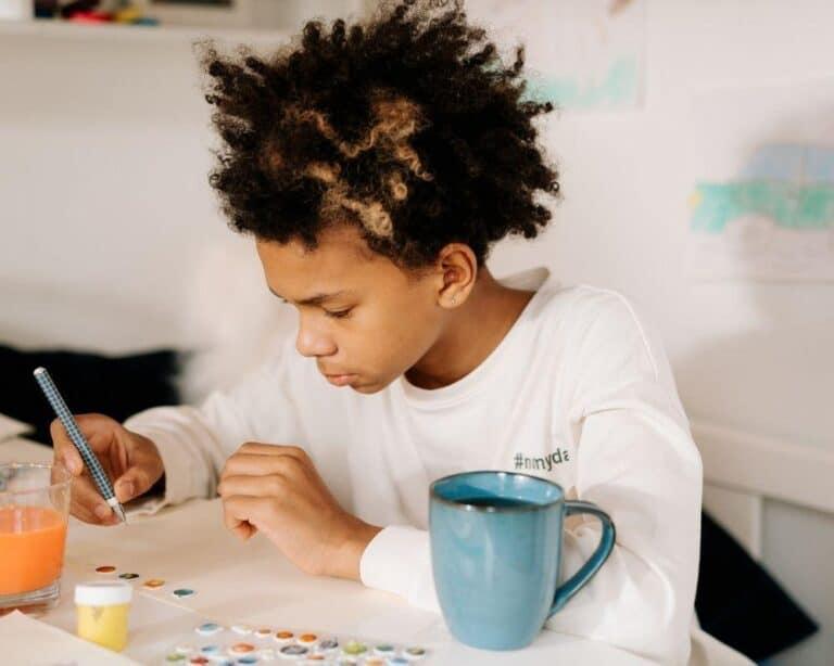 chłopiec siedzi przy stole i maluje