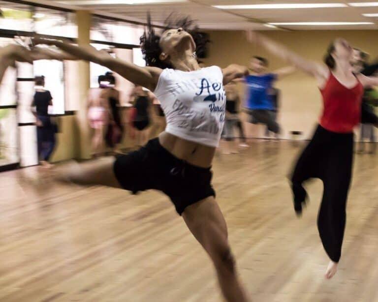 kobieta tańczy na sali a wokół inni tancerze