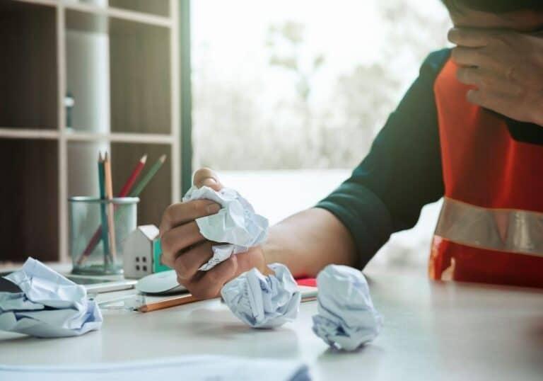 uczeń gniecie papier w kulki przy biurku